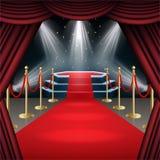 Podium avec le tapis rouge et le rideau dans la lueur des projecteurs Photo stock