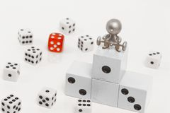 Podium with places on it dice. Figurine of people with a barbell on the podium with places on the background of dice Royalty Free Stock Photography