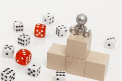 Podium with places on it dice. Figurine of people with a barbell on the podium with places on the background of dice Royalty Free Stock Images