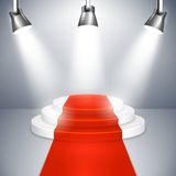 Podium with red carpet. Podium on three elevated circular steps with a red carpet illuminated by three spotlights for an important event  public speaking or Stock Photo