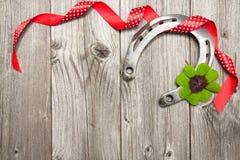 Podkowa, shamrock i czerwień faborek na stary drewnianym, Obraz Royalty Free