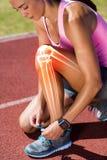 Podkreślać kości wiąże obuwianą koronkę na biegowym śladzie kobieta zdjęcia royalty free