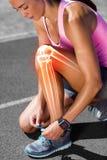 Podkreślać kości wiąże obuwianą koronkę na biegowym śladzie kobieta obrazy royalty free