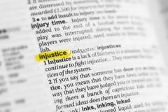 Podkreślający angielszczyzny słowo & x22; injustice& x22; i swój definicja przy słownikiem obrazy stock
