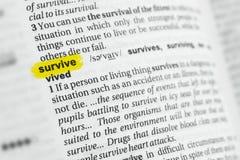 Podkreślający angielszczyzny słowo przeżyje przy słownikiem i swój definicja fotografia stock