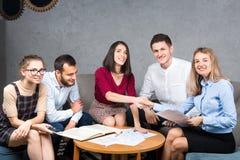 Podległa biznesowa sytuacja, praca zespołowa Grupowi młodzi Kaukascy pięć ludzi siedzi w biurze przy round stołu spotkaniem zdjęcia stock
