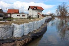 Podmiejscy domy ochraniający z piaskownicy bariery powodzi ochroną od powstającej rzeki fotografia royalty free