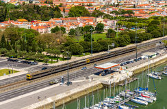 Podmiejski pociąg przechodzi ulicą Lisbon zdjęcia stock