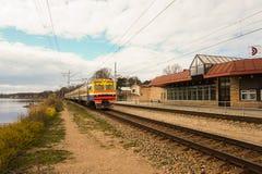Podmiejski pociąg przyjeżdża przy stacyjnym pobliskim jeziorem Fotografia Royalty Free