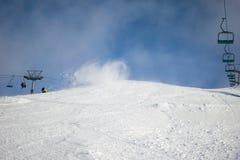 Podmuch wiatru miesza śnieżną pokrywę na narciarskim skłonie obrazy stock