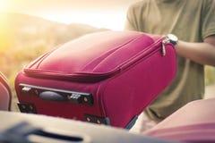 Podnośna różowa walizka w pojazdzie obraz stock