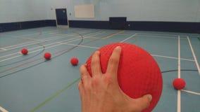 Podnoszący up dodgeball przygotowywającego rzucać je Zdjęcia Stock