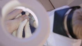 Podologist works with a patient`s thumbnail.The view through the cosmetology magnifying glass.Close-up.Hardware pedicure. Podology stock video footage