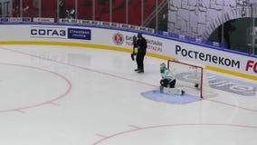 Unidentified reporter filming goalkeeper J. Metsola 77 during hockey game Vityaz vs Salavat Yulayev