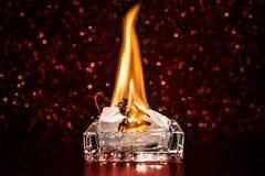 Podpala wśrodku kwadratowego szklanego ashtray w zmroku zdjęcie stock