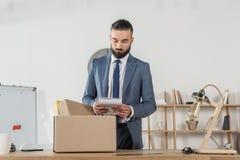 Podpalający smutny biznesmen pakuje biurowe dostawy przy miejscem pracy Zdjęcie Stock