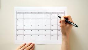 Podpisuje dzień w kalendarzu z piórem, rysuje cwelicha,