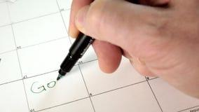 Podpisuje dzień w kalendarzu z piórem, rysuje dobrego złego dzień, zbiory