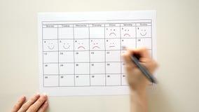 Podpisuje dzień w kalendarzu z piórem, rysuje uśmiech,