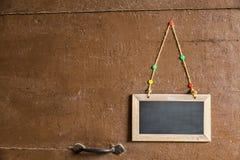 Podpisuje na małym chalkboard wieszającym drewniany drzwi fotografia stock