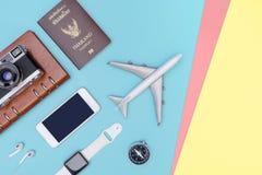 Podróż przedmiotów akcesoria na błękitnym kolorze żółtym różowią tło z paszportową kamerą i samolotem obrazy stock