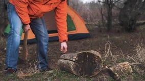 Podróżnik w jaskrawym zima kapeluszu i kurtce ciie łupkę dla robić ogieniowi na tle turystyczny namiot dla zdjęcie wideo