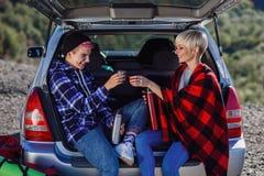 Podróżować, turystyki i przyjaźni pojęcie, Młodzi przyjaciół podróżnicy siedzi na bagażniku samochód i napój gorąca herbata Dwa s fotografia royalty free