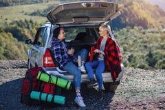 Podróżować, turystyki i przyjaźni pojęcie, Młodzi przyjaciół podróżnicy siedzi na bagażniku samochód i napój gorąca herbata Dwa s fotografia stock