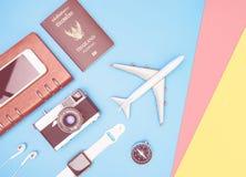 Podróż przedmiotów akcesoria na błękitnym kolorze żółtym różowią tło z paszportową kamerą i samolotem fotografia royalty free