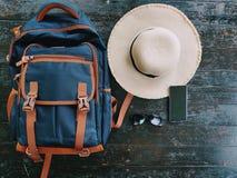 Podróżna torba, kapelusz, słońc szkła, telefon komórkowy, umieszczający na drewnianym stole przygotowywał dla podróżować podczas  obrazy royalty free