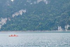 Podróżnicy żeglują pomarańczową łódź w morzu w Thailand Fotografia Stock