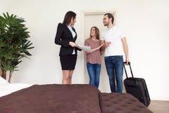 Podróżnicy dobierają się chodzenie w nowym domowym hotelu, opowiada pośrednik handlu nieruchomościami Obraz Stock