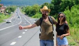 Podróżnicy próbują zatrzymywać samochód Hitchhiking jest jeden tani sposoby podróżować Para autostopowicze podróżuje lato pogodne obrazy royalty free