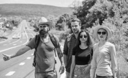 Podróżnicy próbują zatrzymywać samochód Przyjaciół autostopowicze podróżuje lato słonecznego dzień Firma przyjaciół podróżnicy hi zdjęcie stock
