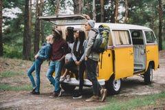 Podróżnicy zbliżają furgonetkę w lesie Zdjęcia Stock