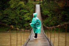 Podróżnicza starsza piękna kobieta w błękit deszczu kurtki krzyża rzece zależącym od mostem w lesie, cieszy się ciszę zdjęcia stock