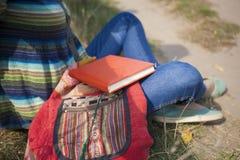 Podróżniczy dziewczyny obsiadanie z książką na naturze Obrazy Royalty Free