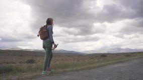 Podróżników napojów woda aktywna dziewczyna turysta z plecakiem i być ubranym przeciw tłu góry okularami przeciwsłonecznymi zbiory wideo