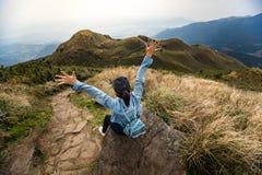 Podróżnik cieszy się po dosięgać szczyt wysoka góra obraz royalty free