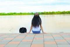 Podróżnik dziewczyna w białym koszulowym obsiadaniu przy cement ziemią Zdjęcie Stock
