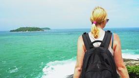Podróżnik dziewczyna z plecak pozycją na plaży i patrzeć w odległość piękny seascape z skałami i morzem zbiory wideo