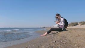 Podróżnik dziewczyna z plecaka obsiadaniem na piaskowatej morze plaży i pisać na maszynie wiadomość na telefonie komórkowym zbiory wideo