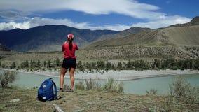 Podróżnik dziewczyna z plecakiem i nakrętką dosięga krawędź góra i brać fotografia Tylny widok, suwak zbiory