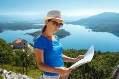 Podróżnik dziewczyny gmerania właściwa wskazówka na mapie, wolności i akcie, Obrazy Royalty Free