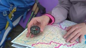 Podróżnik młodej kobiety gmerania kierunek z kompasem na tle mapa w górach zbiory wideo