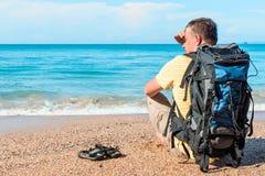 Podróżnik odpoczywa na plaży blisko morza z plecakiem zdjęcie royalty free