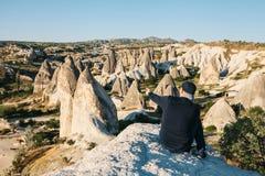 Podróżnik siedzi na górze gór i pokazuje jego rękę przy pięknym widokiem w Cappadocia w Turcja journeyer wędrówki obraz royalty free