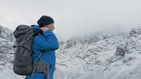 Podróżnik stawia dalej plecaka i iść wycieczkować wzdłuż halnej ścieżki Naprzeciw on są wysocy szczyty zdjęcie wideo