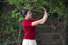 Podr??nik tajlandzka kobieta u?ywa smartphone selfie bierze fotografi? przy widoku punktem Queshi Sceniczny teren przy Shantou mi zdjęcia royalty free