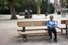 Podróżnik tajlandzka stara kobieta siedzi na ławce przy ogródem przy Speyer miasteczkiem zdjęcia royalty free